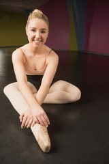 Ballerina sitting and smiling at camera