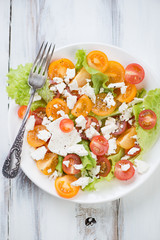 Vegetable salad with various tomatoes and feta, view from above