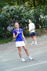 cheerful young woman playing tennis outdoor in summer