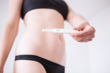 Woman standing and holding a pregnancy test