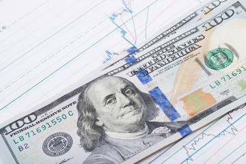 100 USA dollars banknote over stock market chart - studio shot