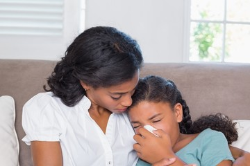 Concerned mother cuddling sick daughter