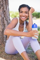 Fit woman sitting against tree holding water bottle
