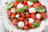 Close-up of caprese salad with capers and green basil leaves