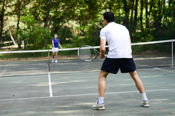 young couple playing tennis outdoor in summer