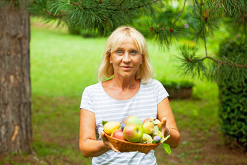 Happy mature woman holding fruits