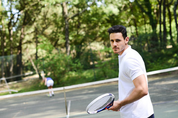 handsome young man playing tennis outdoor in summer