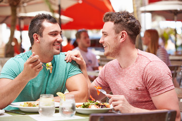 Male Couple Enjoying Lunch In Outdoor Restaurant