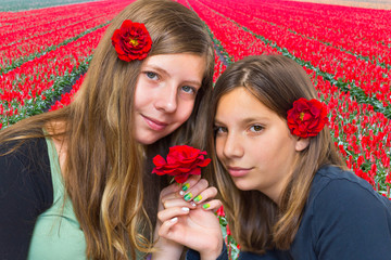 Two girls with red roses in front of tulip field