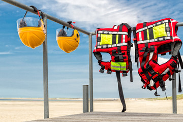 Safety helmets and life jackets hanging on railing