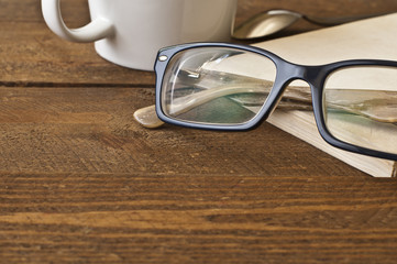 Glasses and book on wood