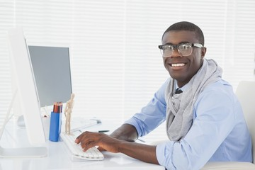 Hipster smiling businessman working at his desk