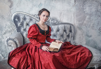 Beautiful woman in medieval dress on the sofa with book
