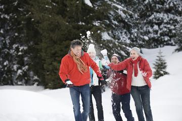 Vier Personen werfen Schnee in der Luft
