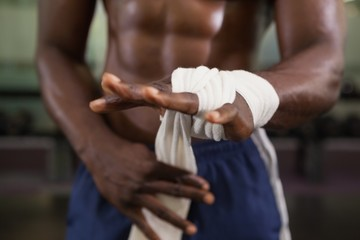 Muscular man binds bandage on his hand