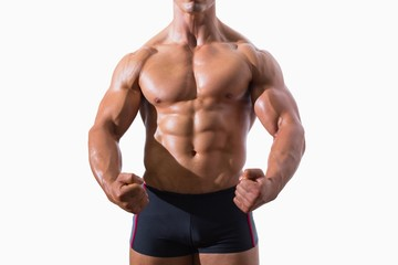 Mid section of a muscular young man clenching fists
