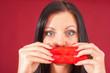 Weibliches Model hält sich eine Paprikaschote vors Gesicht