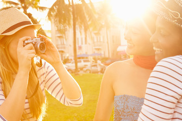 Female Friends Taking Photographs Of Each Other In Park