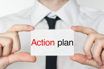 Action plan. Businessman holding business card