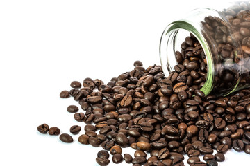 coffee beans spilling out glass bottle on white background