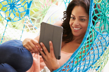 Woman On Outdoor Garden Swing Seat Using Digital Tablet