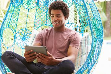 Man On Outdoor Garden Swing Seat Using Digital Tablet