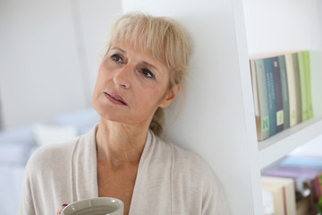 Senior woman standing at home feeling lonely