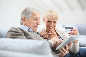 Senior couple e-shopping with digital tablet