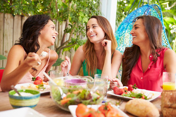 Three Female Friends Enjoying Meal Outdoors At Home