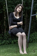Pensive woman sitting on the swing
