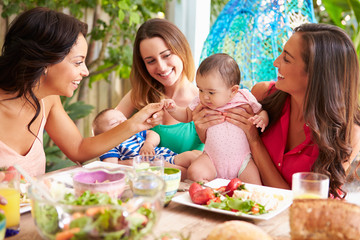 Group Of Mothers With Babies Enjoying Outdoor Meal At Home
