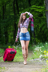Young woman is going on the road and holding a suitcase