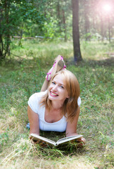 Beautiful girl reading lying on the grass in the forest  whith l