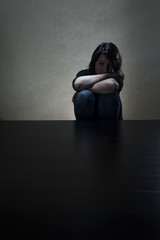 Girl sitting alone in dark room