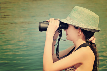 toned image teen girl looking through binoculars side view