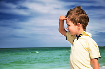 boy looking away from his palm on the background of cloudy sky a