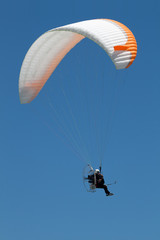 Propelled paraglider on clear sky