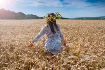 Beautiful girl in  wreath in the field of ripe wheat with lens f