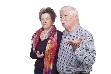 Elderly couple standing with questioning expressions