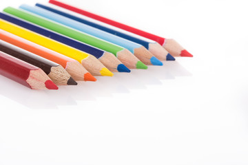 colorful pencils on white with reflection
