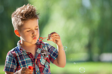 Boy in the park blowing soap bubbles