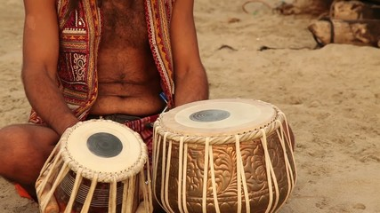 Hippy play on the drum and sit on the beach