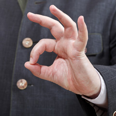 businessman shows OK sign close up