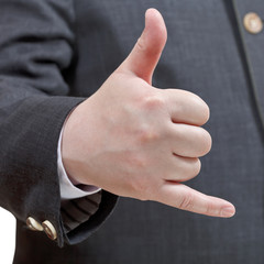 businessman shows phone call sign - hand gesture