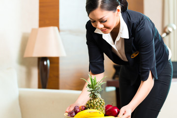 Asian Chinese hotel housekeeper placing fruit