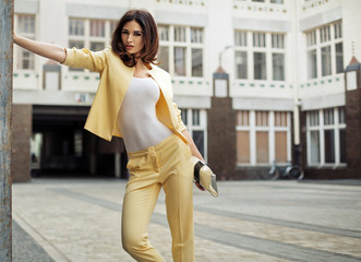 Attractive woman wearing stylish yellow suit