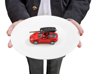 businessman holds white plate with red car and key