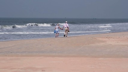 Old couple walk on the beach