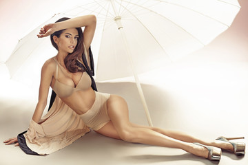Alluring woman lying under the white umbrella