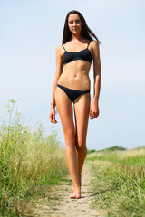 Sexy model in black bikini walking on rural path